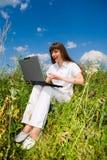 Giovane donna felice sul campo di erba con un computer portatile Fotografia Stock