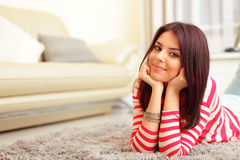 Giovane donna felice sul sofà Immagine Stock