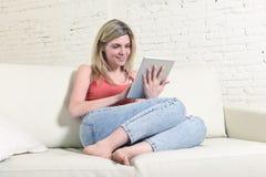 Giovane donna felice sul sofà domestico facendo uso di Internet app sul cuscinetto digitale della compressa immagini stock
