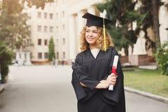 Giovane donna felice sul suo giorno di laurea Immagini Stock