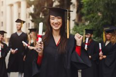 Giovane donna felice sul suo giorno di laurea Immagine Stock