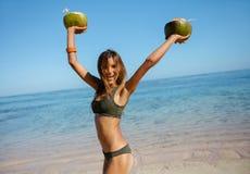 Giovane donna felice sulla spiaggia con le noci di cocco fresche fotografia stock libera da diritti