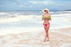 Giovane donna felice topless con le noci di cocco in mani in cappello di paglia con sulla spiaggia con una noce di cocco fotografia stock