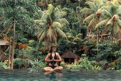 Giovane donna felice in uno stagno tropicale di infinito Località di soggiorno di lusso sull'isola di Bali fotografie stock