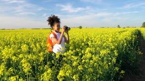 Giovane donna femminile dell'adolescente afroamericano della ragazza della corsa mista con lo zaino arancio e macchina fotografic video d archivio