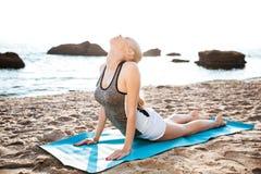 Giovane donna flessibile che fa allungando gli esercizi di yoga Fotografia Stock
