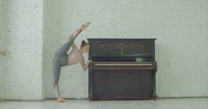 Giovane donna flessibile che fa posa stante di yoga di spaccatura