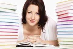Giovane donna fra la lettura delle pile di libri. Fotografia Stock
