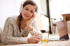 Giovane donna fresca che si trova sul pavimento che ascolta la musica con le cuffie Immagini Stock