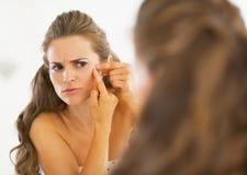 Giovane donna frustrata che schiaccia acne Fotografie Stock Libere da Diritti