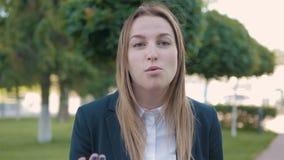 Giovane donna frustrata di affari che grida sulla macchina fotografica all'aperto, concetto emozionale archivi video