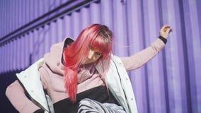 Giovane donna funky felice con capelli rosa che ballano sul fondo colorato Bella donna che balla vicino al contenitore porpora in archivi video