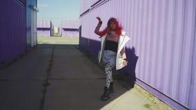 Giovane donna funky felice con capelli rosa che ballano sul fondo colorato Bella donna che balla vicino al contenitore porpora in stock footage