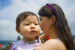 Giovane donna giapponese asiatica graziosa felice come madre di amore che tiene la neonata adorabile della figlia durante l'escur fotografia stock libera da diritti