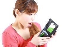 Giovane donna giapponese che esamina il suo portafoglio vuoto Immagine Stock