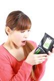 Giovane donna giapponese che esamina il suo portafoglio vuoto Fotografia Stock Libera da Diritti
