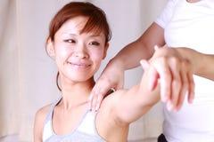 Giovane donna giapponese che ottiene chiroterapia Immagini Stock