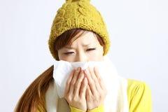 Giovane donna giapponese che starnutisce nel tessuto Fotografia Stock