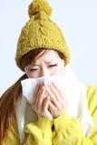 Giovane donna giapponese che starnutisce nel tessuto Immagini Stock