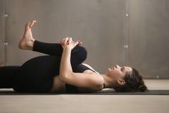 Giovane donna in ginocchia al petto, posa di Apanasana, studio, primo piano Immagini Stock