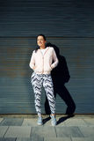 Giovane donna graziosa in abbigliamento di sport che posa sul fondo nero della parete pronto per un allenamento Immagini Stock
