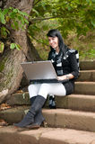 Giovane donna graziosa al parco di autunno con il computer Immagini Stock Libere da Diritti