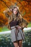 Giovane donna graziosa alla sosta di autunno Immagini Stock
