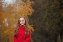 Giovane donna graziosa alla sosta di autunno Immagine Stock