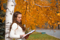 Giovane donna graziosa alla sosta di autunno Immagini Stock Libere da Diritti