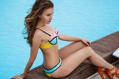 Giovane donna graziosa in bikini luminoso di estate vicino allo stagno fotografia stock