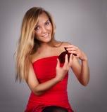 Giovane donna graziosa bionda con il biglietto di S. Valentino presente in mani in re Fotografie Stock
