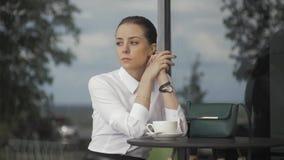 Giovane donna graziosa in caffè della via con la tazza archivi video