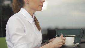 Giovane donna graziosa in caffè della via con la tazza stock footage