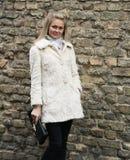Giovane donna graziosa in cappotto di pelliccia con la frizione immagine stock