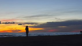Giovane donna graziosa che cammina dalla spiaggia su un bello tramonto stock footage
