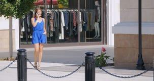 Giovane donna graziosa che cammina giù la strada dei negozi stock footage