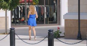 Giovane donna graziosa che cammina giù la strada dei negozi archivi video