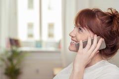 Giovane donna graziosa che chiacchiera sul suo cellulare Fotografia Stock