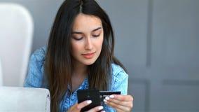 Giovane donna graziosa che compra online con la carta di credito e lo smartphone che si trovano su uno strato nel salone a casa stock footage