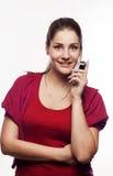 Giovane donna graziosa che comunica sul telefono Immagini Stock