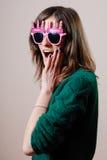 Giovane donna graziosa che esamina macchina fotografica in lavori o indumenti a maglia Fotografia Stock