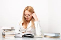 Giovane donna graziosa che impara alla tabella con i libri Immagine Stock Libera da Diritti
