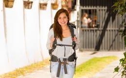Giovane donna graziosa che indossa abbigliamento casuale e zaino che stanno davanti alla macchina fotografica che sorride felicem Fotografie Stock