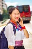 Giovane donna graziosa che indossa blusa andina tradizionale e zaino blu, bus aspettante al binario della stazione di aria aperta Immagine Stock
