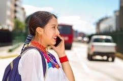 Giovane donna graziosa che indossa blusa andina tradizionale e zaino blu, bus aspettante al binario della stazione di aria aperta Immagini Stock