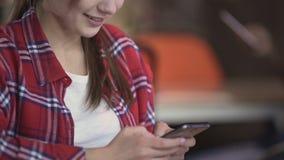 Giovane donna graziosa che manda un sms sullo smartphone in caffè, free lance su una rottura stock footage