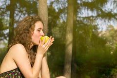 Giovane donna graziosa che mangia mela su un campo Fotografia Stock