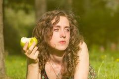 Giovane donna graziosa che mangia mela su un campo Immagini Stock