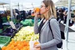 Giovane donna graziosa che odora arancio nel mercato di strada immagini stock