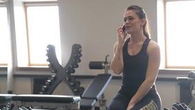 Giovane donna graziosa che parla dal telefono che si siede nello studio di forma fisica archivi video